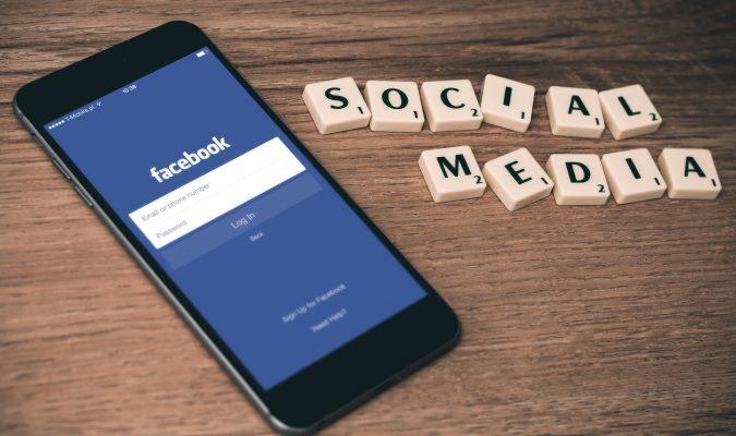 """Fotografia di uno smartphone e scritta """"social network"""" fatta con tasselli scarabeo"""