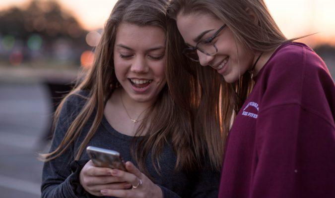 Fotografia di due ragazze che guardano uno smartphone
