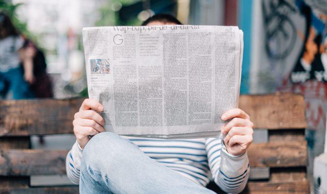 Fotografia di un uomo seduto che legge il giornale