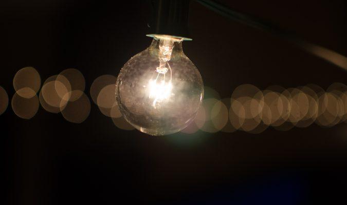 Fotografia di una lampadina accesa in un contesto di buio