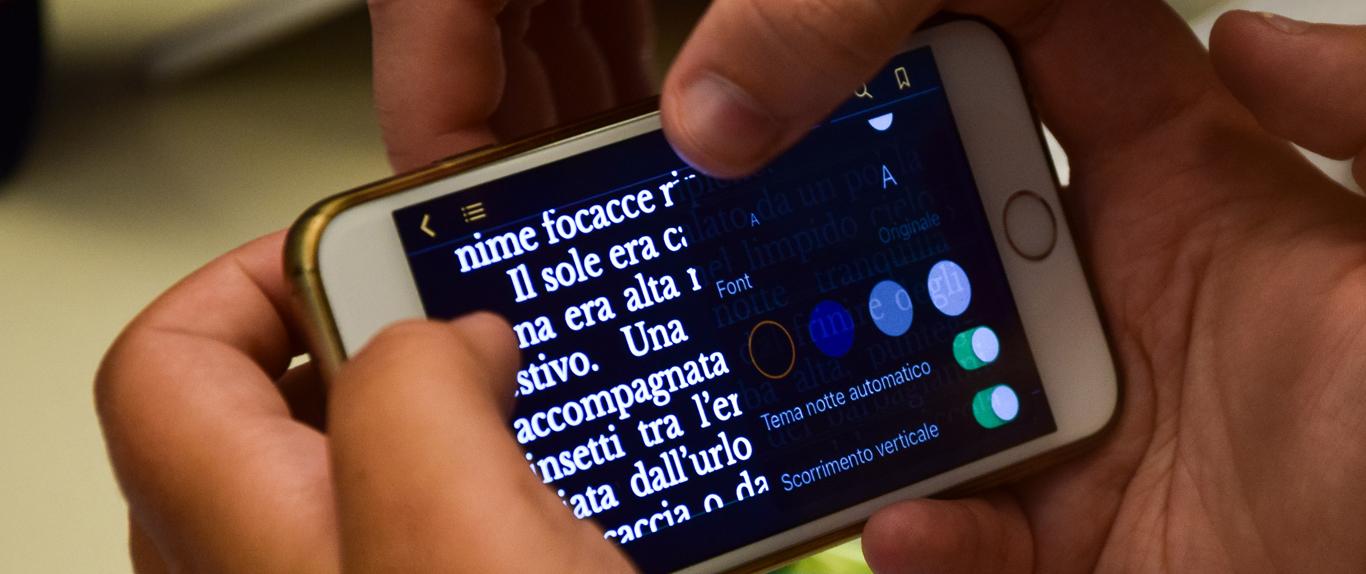 Fotografia di mani che usano smartphone. In primo piano sullo schermo un testo e le opzioni per personalizzare la visualizzazione