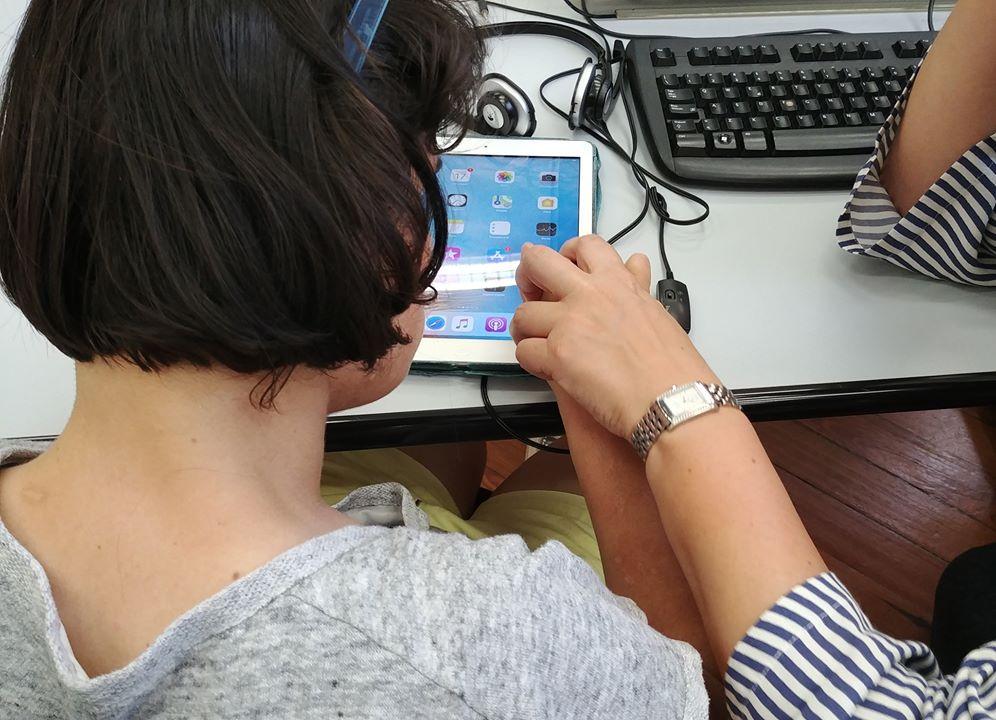 Fotografia di una ragazza di spalle mentre utilizza un device aiutata da un formatore LIA