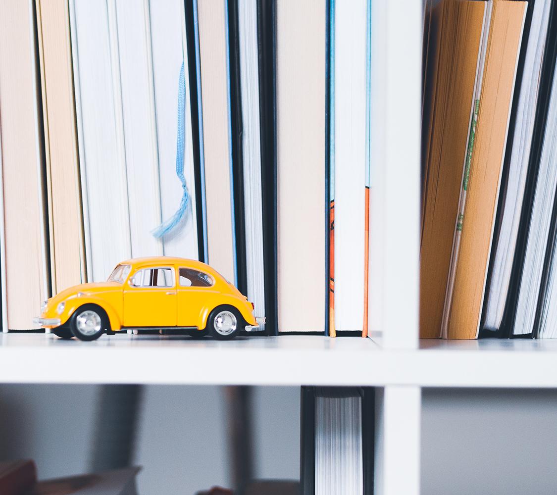 Fotografia di uno scaffale di libri con in primo piano il modellino di un maggiolino