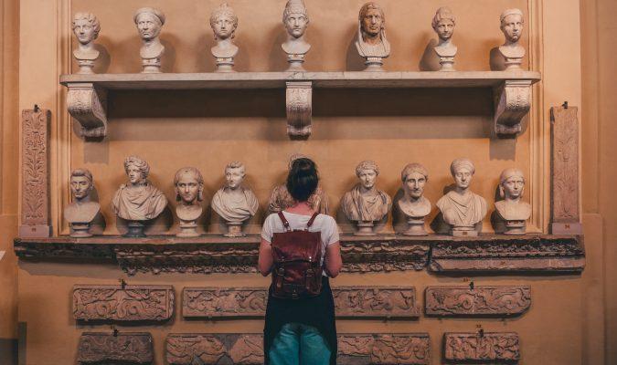 Fotografia di una ragazza di spalle di fronte a dei busti marmorei