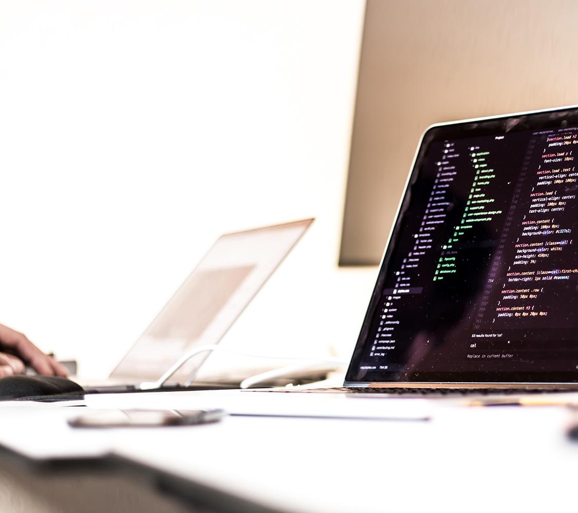 Fotografia di un computer su un tavolo. Sullo schermo codice di programmazione