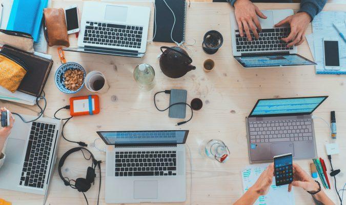 Fotografia di tavolo con laptop e smartphone e persone al lavoro