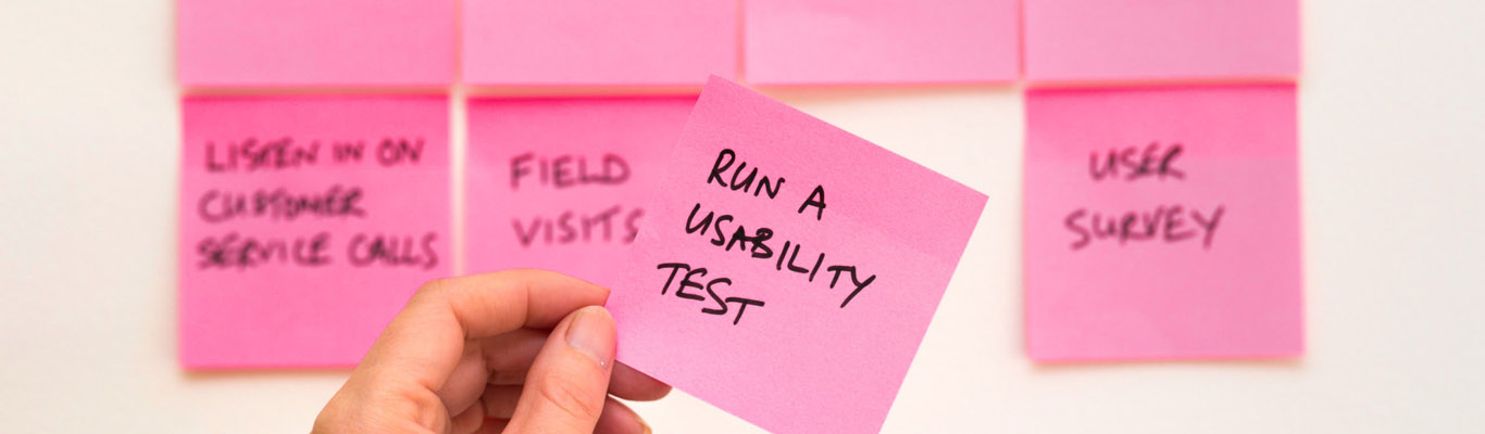 Fotografia di una mano che regge un post-it con la scritta run a usability test