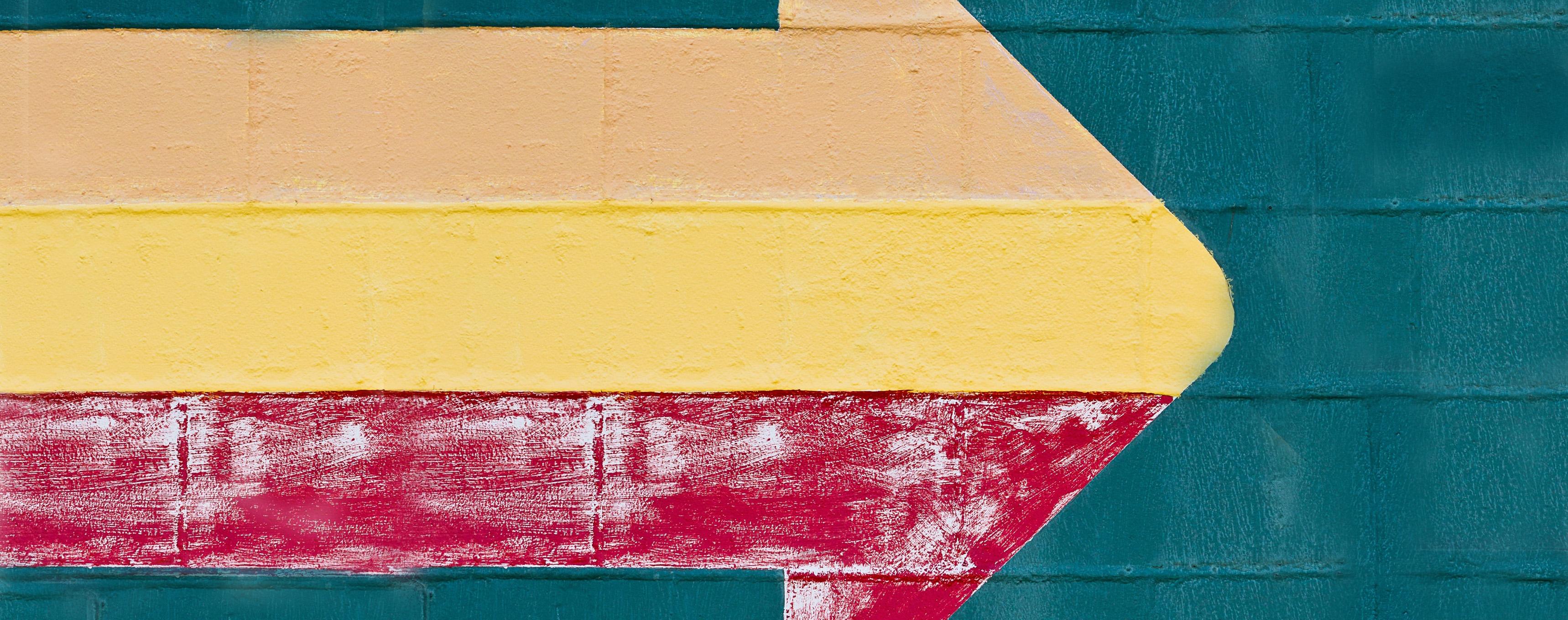 Fotografia di un muro su cui è disegnata una freccia