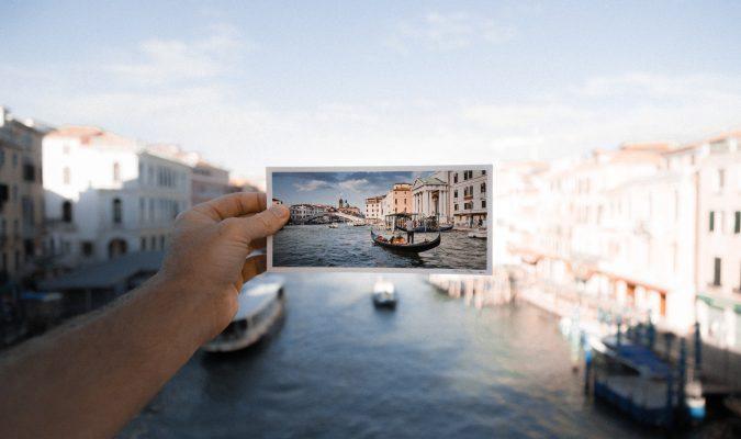 fotografia in cui una mano regge su uno sfondo di Venezia un'immagine cartacea della stesso scorcio
