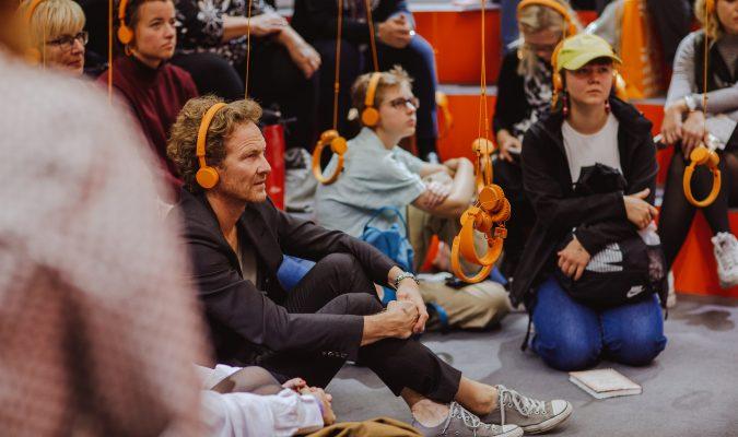 Fotografia di persone sedute a terracon cuffie per l'ascolto