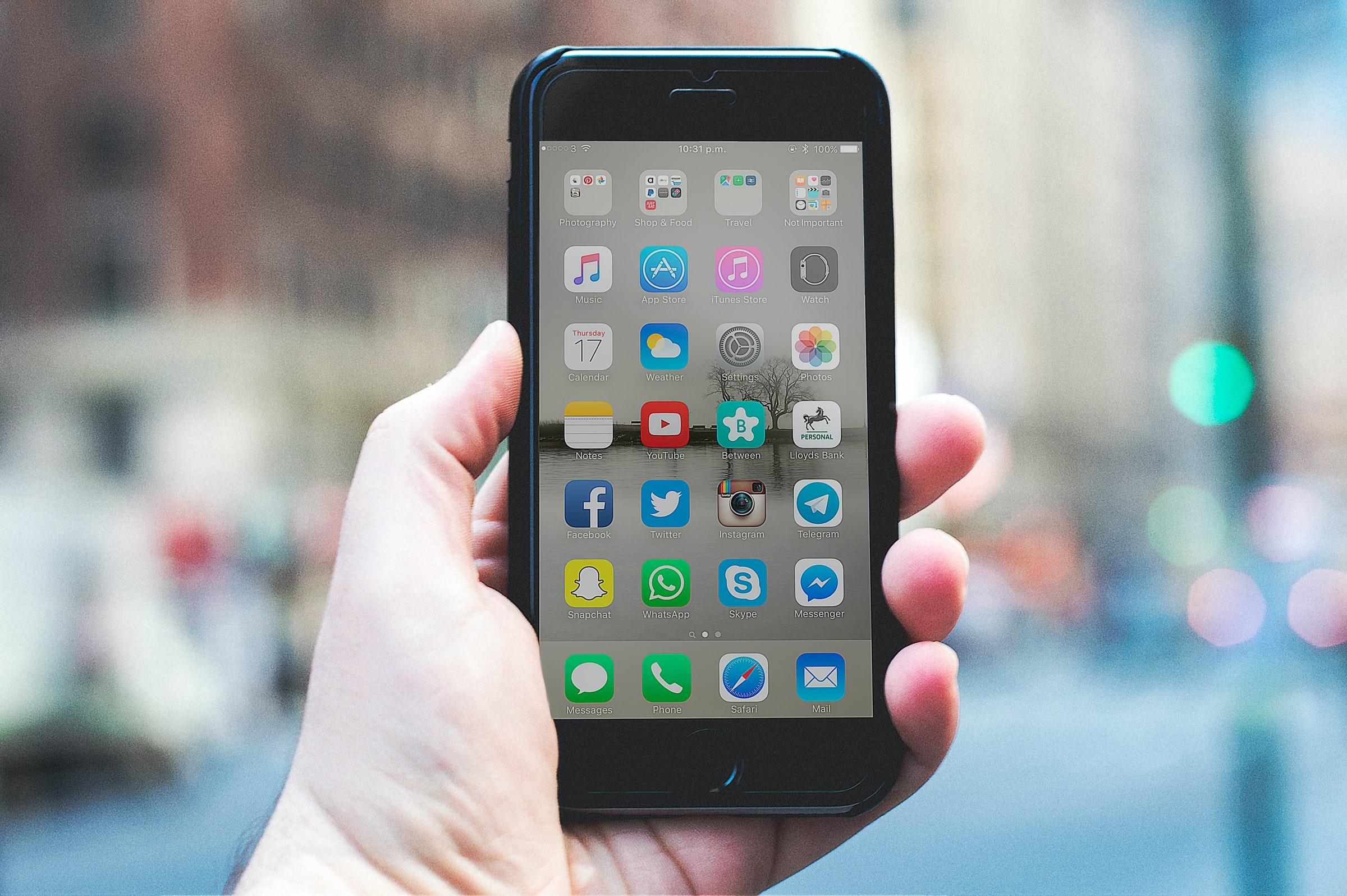 Fotografia di una mano che regge uno smartphone con schermo acceso