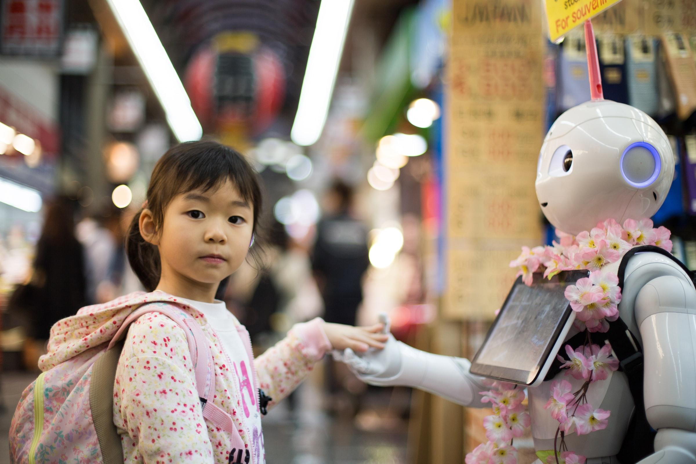 Fotografia di un robot con sembianze umane che porge la mano a una bambina