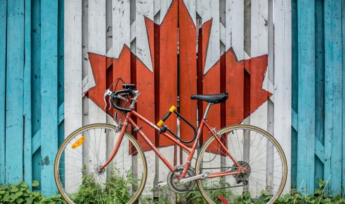 Photo of a byclicle leaning on a mural of a maple leaf