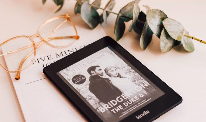 Fotografia di un Kindle e un paio di occhiali su un tavolo