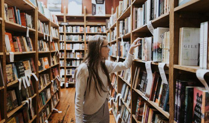 Fotografia di una ragazza che consulta dei libri su uno scaffale