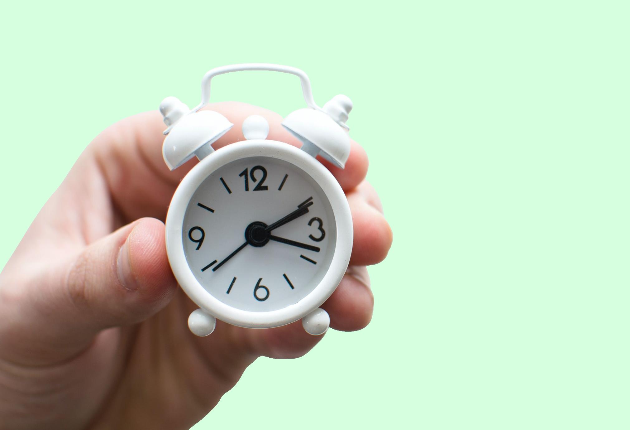 Fotografia di una mano che regge un orologio sveglia