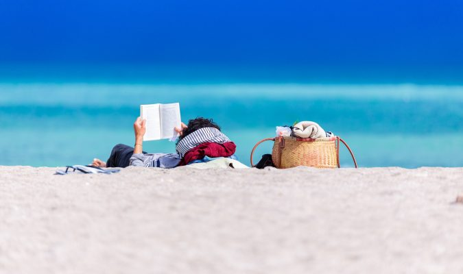 photo of a man reading a book by the sea