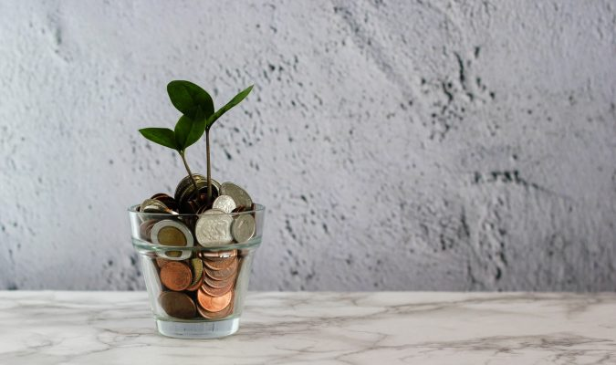 photograph of a jar full of coins from which sprout a plant