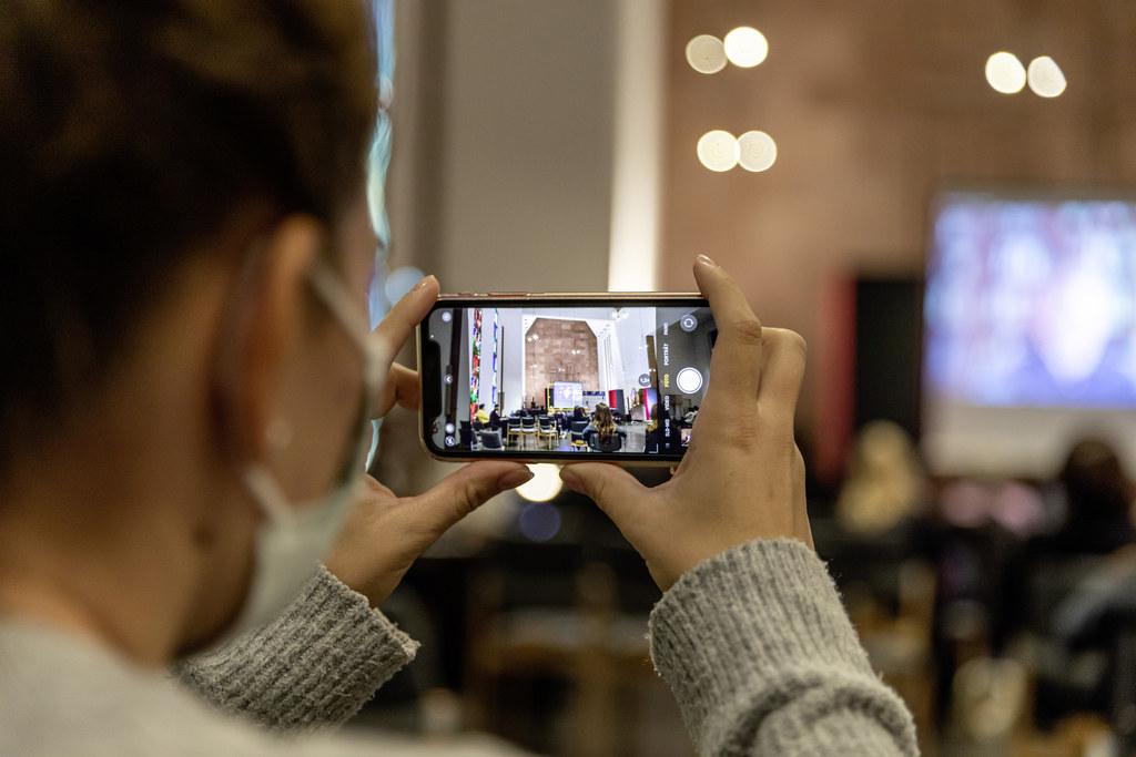 Fotografia di una persona di spalle che sta fotografando una conferenza con uno smartphone